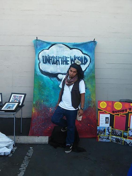 Artist Ivan Rueda-Pineda in front of Skid Robot's backdrop
